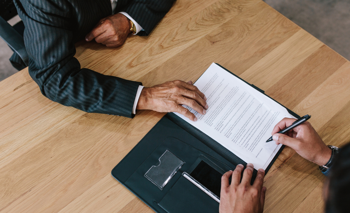 Overview shot of one person offering the other a contract on a wooden table.